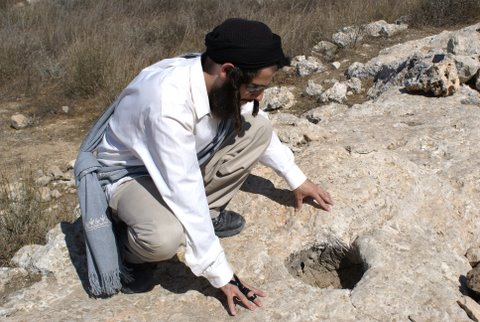 Looking closely at what is understood to be one of the holes for the original stakes by which the roof of Mishkan Shilo was tethered down. *